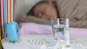 I förgrunden finns mediciner och näsdukar på ett bord, i bakgrunden ligger en förkyld man i sin säng