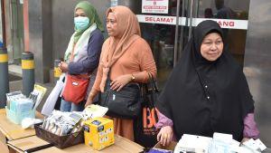 Tre kvinnliga gatuförsäljare. Bara en av dem har ansiktsmask.
