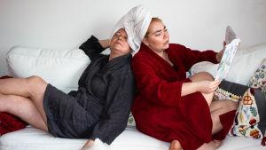 Heidi och Vivi sitter i badrockar i soffan med håret invirade i handdukar.