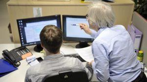 Två personer sitter vid en dator.