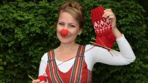 Nainen pitää puolivalmistatutunt villasukkaneuleprojekt kädessä