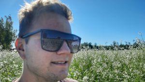 En ung jordbrukare med spegelglasögon står på en äng med oljerättika