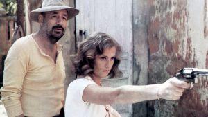 Auringonpimennys-elokuvassa Philippe Noiretin ja Isabelle Huppertin esittämät hahmot seisovat ulkona, nainen pitää asetta kädessään ja osoittaa sillä jotain.