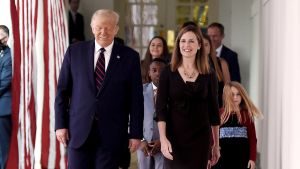 USA:s president Donald Trump går bredvid Amy Coney Barrett. Båda ler. Bakom dem står Coney Barretts barn.