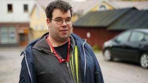 En man med kort mörkt hår och glasögon. Han står ute på en innergård med parkerade bilar och hus i bakgrunden.