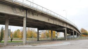 en cementbro som leder över järnväg och väg