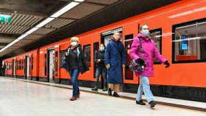 Människor i munskydd går ut ur en metro i Helsingfors.