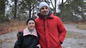 Äldre kvinna och medelålders man ser in i kameran.