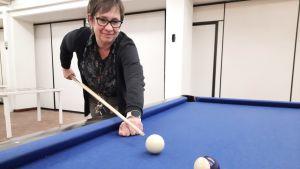 En kvinna med glasögon står redo att skjuta en billjarboll med en kö.