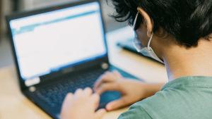 En elev använder en laptop. Han bär munskydd.