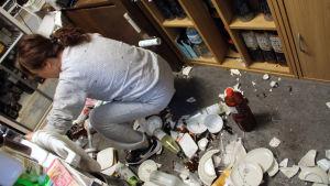 Kvinna sopar upp sönderslagna tallrikar på en restaurang, efter jordskalv i Fukushima 13.2.2021