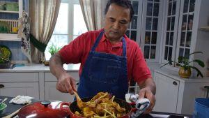 En man som rör om i en gryta i ett kök