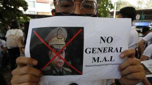 Demonstranter i Myanmars grannland Thailand visar upp en bild av juntans ledare, general Min Aung Hlain.