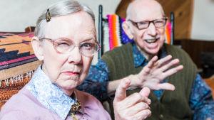 Bister äldre dam och skrattande gubbe i soffa