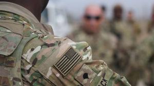 En amerikansk soldat syns på bilden. Bilden är en närbild så bara soldatens axem pch sidan av huvudet syns.