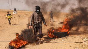 En palestinsk demonstrant bränner bildäck vid Gazaremsan den 10 maj 2021.