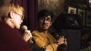 Ulrika Gustafsson och Adrian Perera diskuterar på en scen.