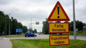 Ett trafikmärke där det står farlig korsning. I bakgrunden syns en bil som är påväg ut i en korsning.