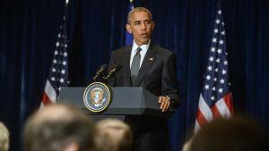 USA:s president Barack Obama bakom ett podium med USA:s och EU:s  flaggor i Bakgrunden. Obama fördömde dödsskjutningarna av poliser i Dallas under inledningen av Nato-toppmötet i Warszawa, Polen.