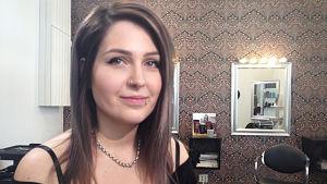 Kvinna småler mot kameran i frisörsalong