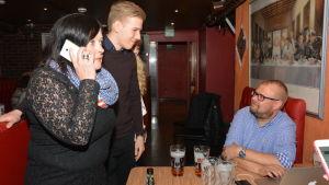 Sari Wilhola står och pratar i telefonen. Bredvid henne står Rasmus Ulonen och vid ett bord sitter Marko Rautakoura.