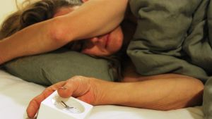 Nainen nukkuu sängyssä herätyskello kädessä.