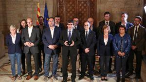 Kataloniens regionpresident Carles Puigdemont, flankerad av sin regering, håller tal efter folkomröstningen om självständighet.