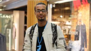 Saeed Aidarous står framför ett skyltfönster.