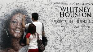 Två personer skriver på Whitney Houstons minnesmärke.