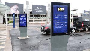 Skyltar med taxipriser vid Helsingfors-Vanda flygplats.