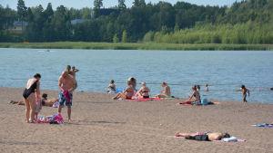 Många människor ligger på en sandstrand och solar sig. Några barn leker i vattnet.