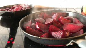 Rödbetor som steks i en panna på spisen.