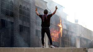 En demonstrant står utanför en brinnande statlig byggnad