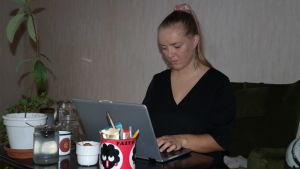 Julia Degerth sitter vid en dator och bloggar