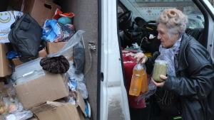En äldre dam lastar in matvaror i skåpbil