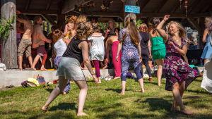 Ihmisiä tanssimassa nurmella ja ulkokatoksessa