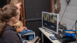 Tre personer sitter och tittar på en monitor.