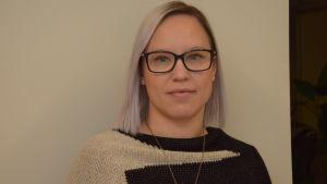 En kvinna med glasögon och ljust hår fotad inomhus mot en beige-grå vägg.