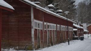 Lagerbyggnader i trä, rödmyllade, i ganska dåligt skick. Vinter och snö