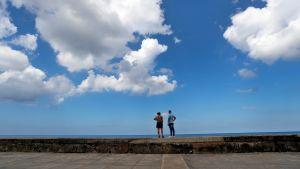 Ett par står på en mur och tittar på havet.