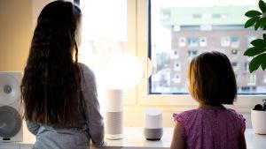 Två flickor i ca 6 och 9 årsåldern står vid ett fönster med ryggen till kameran och har två smarthögtalare framför sig som de talar till