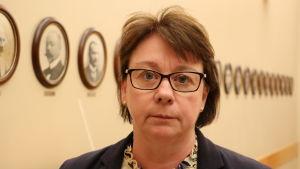 En kvinna med kort mörkt hår och glasögon står intill en vägg som är prydd med porträttbilder.