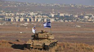 Ett gammal israelisk stridsvagn står på en sluttning i Golan med utsikt över gränsen mot Syrien och den syriska staden Quneitra.