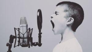 Nuori poika laulaa mikrofoniin