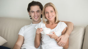 en ung man sitter på en soffa och håller om en medelålders kvinna