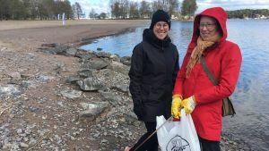 outi och mari pajala står vid stranden vid runsala folkpark med en soppåse med skräp i händerna