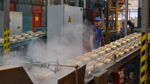 En man som står vid ett band på äggkartongsfabriken