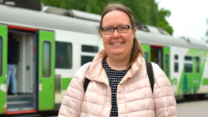 Kvinna i ljus jacka står framför ett tåg på en perrong. Hon ler mot kameran.