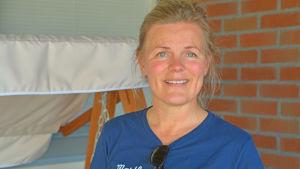 Kvinna ler vid tegelvägg