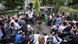 Sarah Sanders omringad av journalister, mikrofonstänger och kameror på Vita husets gård.